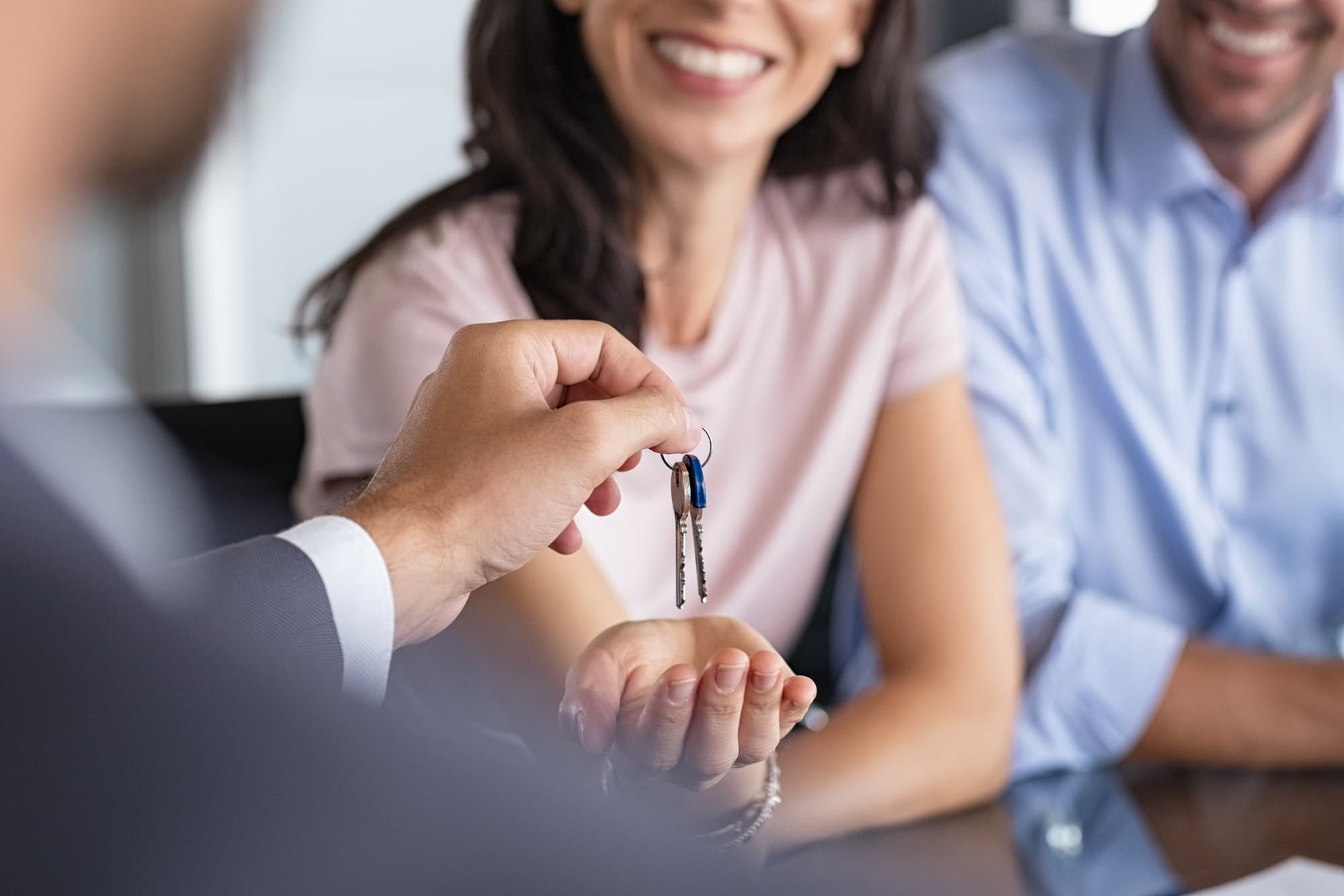 Real estate agent giving house keys to woman